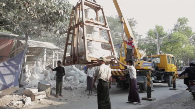 ws, tu a completed buddha statue is lifted by crane onto a truck / mandalay, myanmar - ミャンマー点の映像素材/bロール