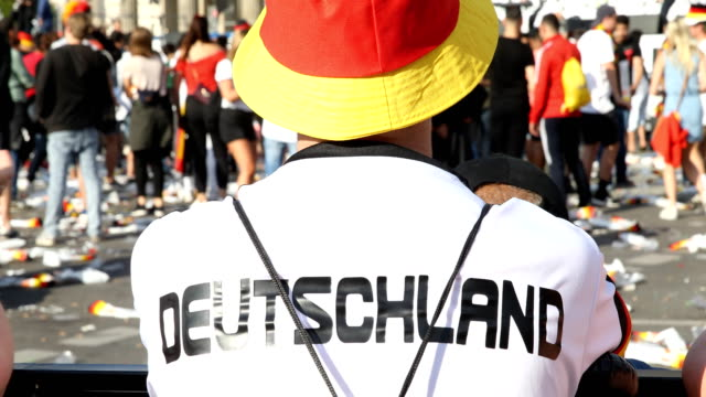Completely disappointed fan in a Germany jersey and hat in the colors of the German flag on the fan mile at the Brandenburg Gate after the historic...