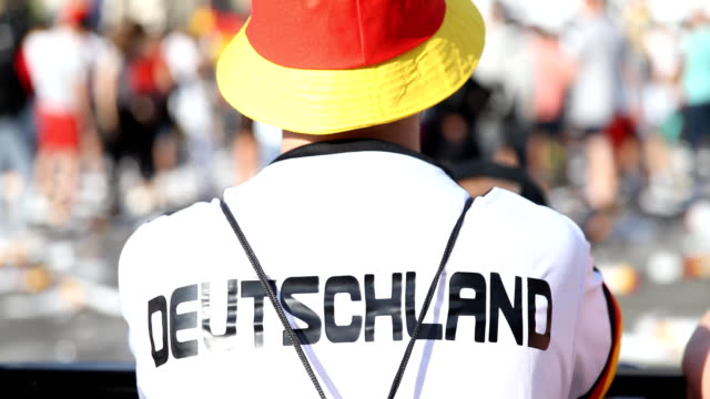 vídeos de stock e filmes b-roll de completely disappointed fan in a germany jersey and hat in the colors of the german flag on the fan mile at the brandenburg gate after the historic... - equipamento de equipa