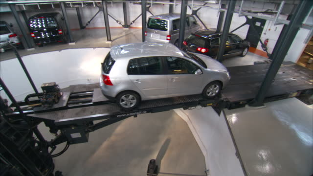 a complex hydraulic platform lifts a car into the air inside a tower parking garage. - hydraulic platform stock videos & royalty-free footage