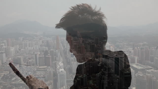 composite image of man using tablet device and city - multi layered effect点の映像素材/bロール
