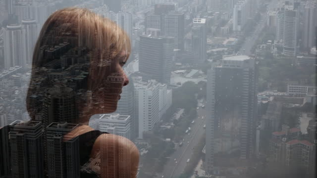 composite image of woman looking out over city - multi layered effect点の映像素材/bロール