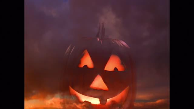 vídeos de stock, filmes e b-roll de composite medium shot lit up jack o'lantern pumpkin with time lapse clouds in background - halloween background