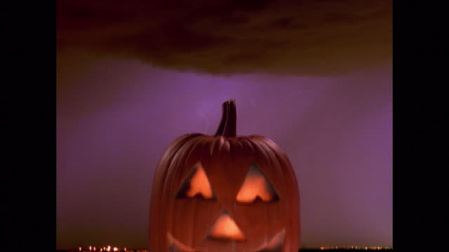 composite medium shot lit up jack o'lantern pumpkin with time lapse lightning in background - jack o' lantern stock videos and b-roll footage