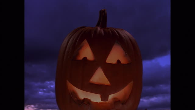 composite medium shot lit up jack o'lantern pumpkin with time lapse clouds and lightning in background - jack o' lantern stock videos and b-roll footage