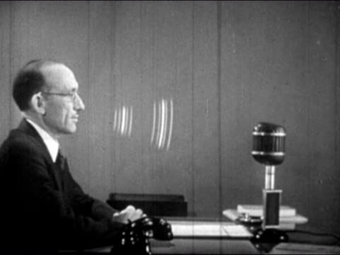 1943 Composite medium shot man sitting at desk speaking as soundwaves move from his mouth to microphone