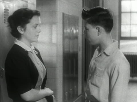 1955 composite medium shot side view of teenage boy and girl talking in school corridor with superimposed breath clouds / audio - 14歳から15歳点の映像素材/bロール