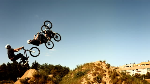 hd slow motion: composite shot of a backflipping dirt jump - bmx cycling stock videos and b-roll footage