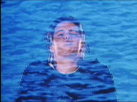 vídeos de stock, filmes e b-roll de 1987 composite young woman holding breath with animation of water and fish superimposed over her - prendendo a respiração