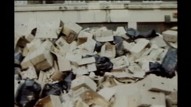 vídeos y material grabado en eventos de stock de union leaders predict industrial unrest 1970s massive pile of uncollected rubbish during winter of discontent strikes cleaner spraying rubbish with... - 1970
