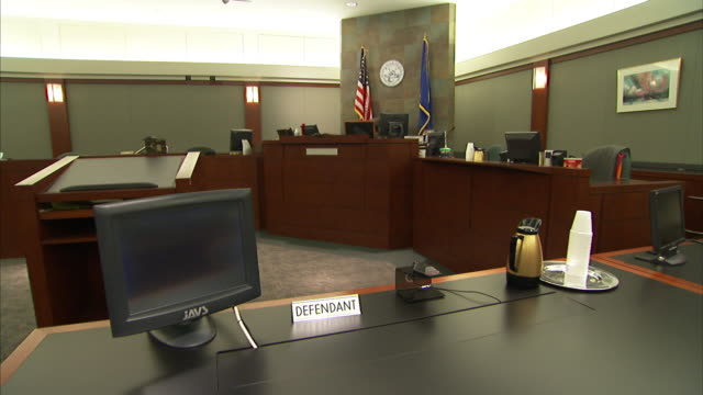 A computer and coffee carafe occupy the defendant's table in a courtroom.