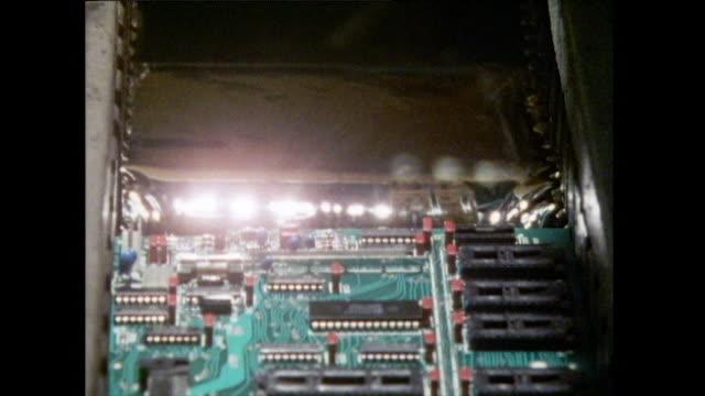 stockvideo's en b-roll-footage met computer circuit board is dipped in solder bath; 1986 - tonen