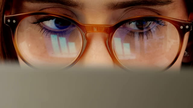 Computer data close up, woman wearing glasses.
