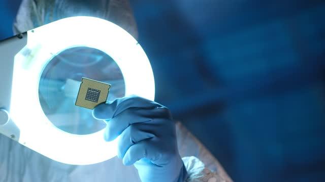 stockvideo's en b-roll-footage met de ingenieur die van de computer centrale eenheid van de verwerking, cpu onder vergrootglas in een laboratorium houdt. - vergrootglas