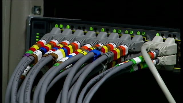 london int ethernet ables plugged into computer equipment and lights flickering / cables leading to computer equipment / scrolling digital readout on... - flüssigkristallanzeige stock-videos und b-roll-filmmaterial