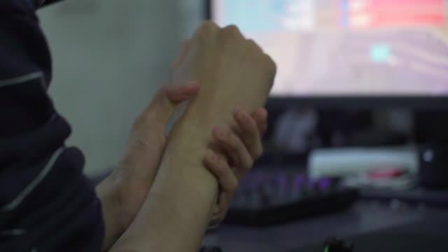 Computer gamer massages wrist, close up