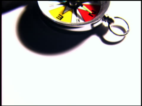 vídeos de stock, filmes e b-roll de computer generated image close up tilt up over compass on white background - enfoque de objeto sobre a mesa