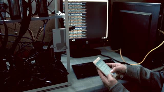 stockvideo's en b-roll-footage met computer hacker met slimme telefoon computer programmeertaal op computer, real-time - mining