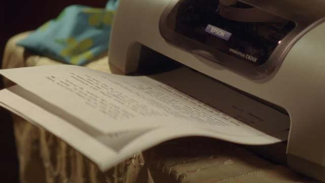 A computer printer completes a document.