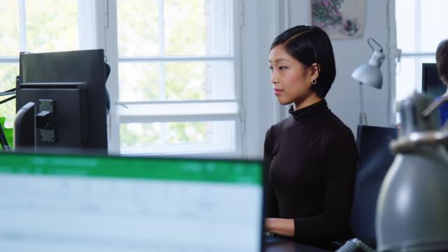 彼女の机で働くコンピュータプログラマー - desktop pc点の映像素材/bロール