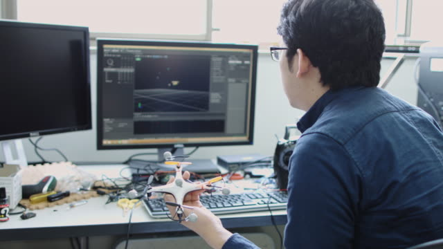 computer science student using drone and computer - エンジニア点の映像素材/bロール