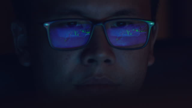 computer screen light reflects from glasses. close up of eyes. businessman, coder or programmer working late at night with a laptop. thoughtful focused guy in dark. reflection of the monitor. - spectacles stock videos & royalty-free footage