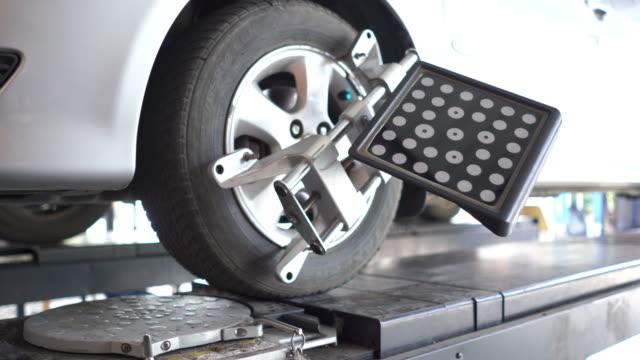 vidéos et rushes de informatisé équilibrant une roue de voiture - mécanicien