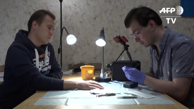 vídeos de stock e filmes b-roll de con un escalpelo vladislav zaitsev hace una incision entre el dedo indice y el pulgar del paciente e introduce un pequeno cilindro de vidrio un chip... - dedo humano