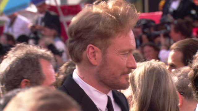 hd cu conan o'brien speaking to unknown person looking around and moving through dense crowd on the red carpet - conan o'brien stock videos and b-roll footage