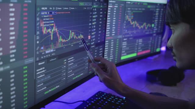 vidéos et rushes de concentré homme asiatique assis près d'ordinateur de bureau en utilisant l'investissement d'écran d'ordinateur avec des données boursières à la maison - marché boursier