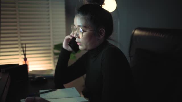 vidéos et rushes de femme d'affaires asiatique concentrée travaillant tard avec son ordinateur. - bring your own device