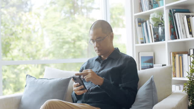 vídeos de stock e filmes b-roll de concentrated asian man using mobile phone to make payment. - one mature man only