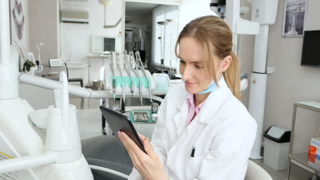 concentrated dentist working on tablet - surgical mask stock videos & royalty-free footage