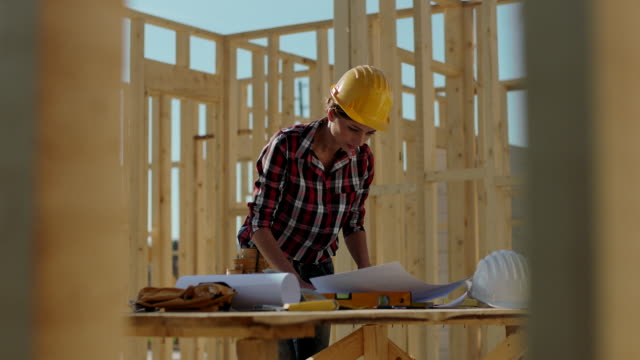 Concentrated female architect looking blueprints at construction site