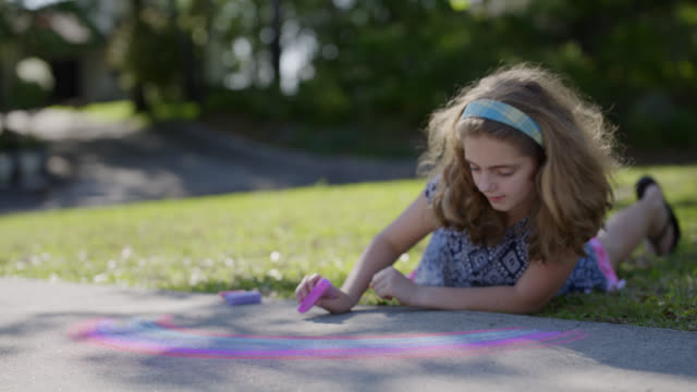 ls concentrated girl focuses on drawing a chalk rainbow on her driveway - driveway stock videos & royalty-free footage