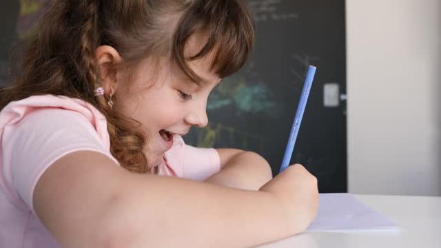集中した小さな女の子は絵を描いている間笑う - dia点の映像素材/bロール