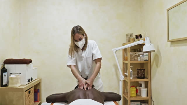 concentrated massage therapist working on patient - massage table stock videos & royalty-free footage
