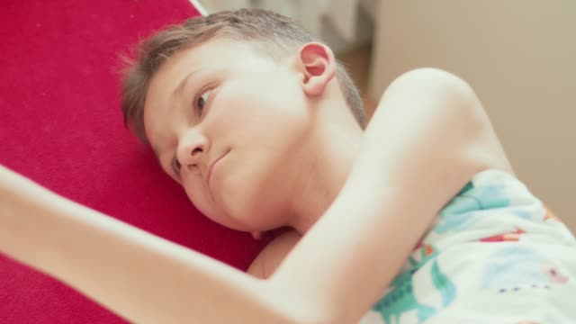 concentrated teenager boy under blanket reading book lying in bed - un ragazzo adolescente video stock e b–roll