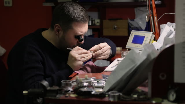 concentrated watchmaker repairing vintage pocket watch at workshop - lens optical instrument stock videos & royalty-free footage