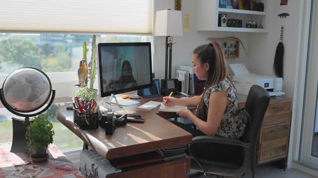 vidéos et rushes de concentrated woman has a discussion with a coworker over a virtual call - bureau ameublement