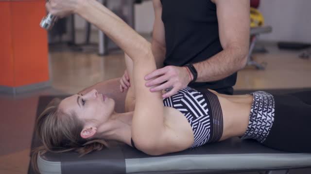 Geconcentreerd vrouw opheffing halters met instructeur