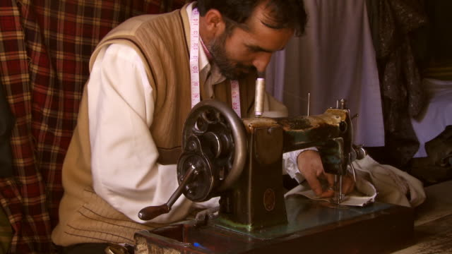 Concentrating tailor sewing hem