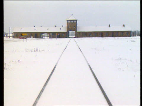 concentration camp reparations promised lib auschwitz tower as railway line disappears thru entrance into camp track fade to barbed wire through... - ferrovia video stock e b–roll