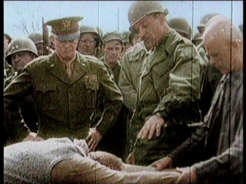 vídeos de stock e filmes b-roll de / concentration camp victims released from camp / soldiers walking through concentration camp / close up of dwight eisenhower / man stretched out as... - nazismo