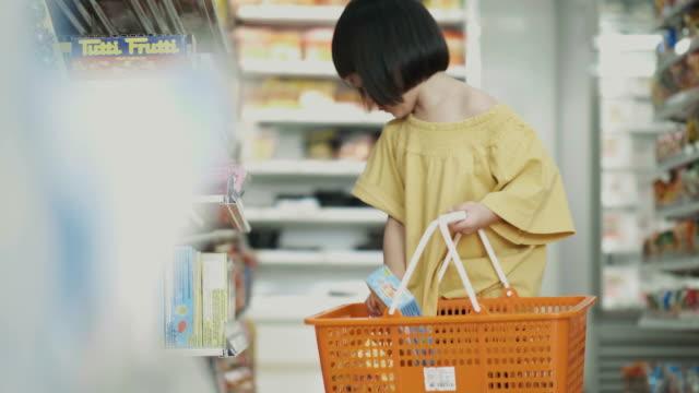 Konzentration von kleines Thai Mädchen ist die Auswahl und einige Lebensmittel im Supermarkt kaufen