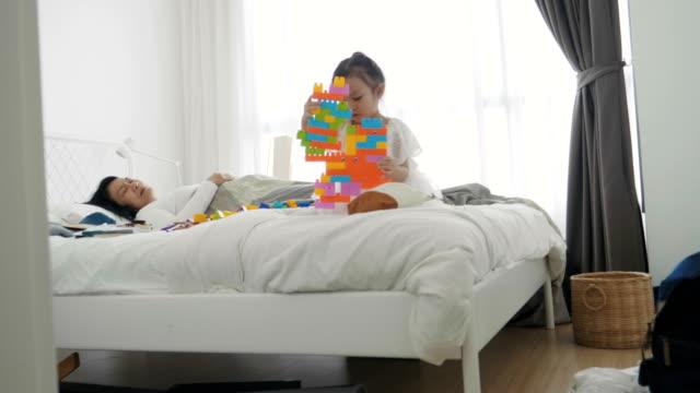 konzentration von thai mädchen spielt klötzchen, während mutter auf dem bett im schlafzimmer schläft - spielzeug stock-videos und b-roll-filmmaterial