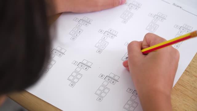 stockvideo's en b-roll-footage met concept homeschooling in de aziatische familie met één kind.  direct boven close-up mening over de schouder van een jongen teenage jongen die online onderwijs in de woonkamer van hun huis als homeschool leert. schooljongen praktijk wiskunde en huiswerk. - exam