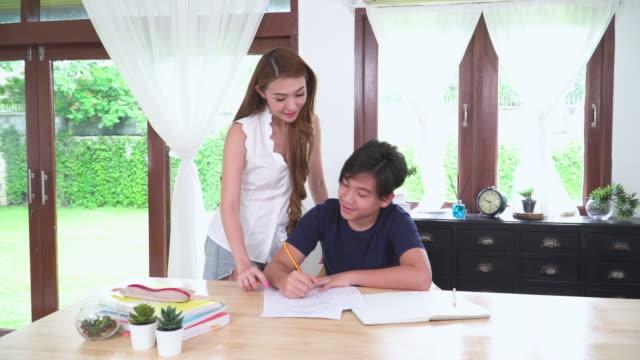 stockvideo's en b-roll-footage met concept homeschooling in de aziatische familie met één kind. vooraanzicht van de zoon, jongen tiener, een schooljongen leren en het beoefenen van pythagoras wiskunde en huiswerk in de woonkamer van het huis en alleenstaande moeder komen om te zien wat ze - 14 15 years
