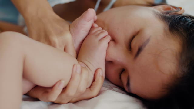 Concept of love and family. Mother kissing foot her baby