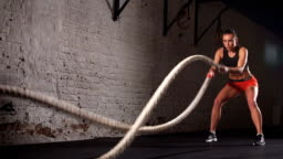 Concept: power, strength, healthy lifestyle, sport. Powerful attractive muscular woman gym trainer do battle workout with ropes at the gym. Slow motion